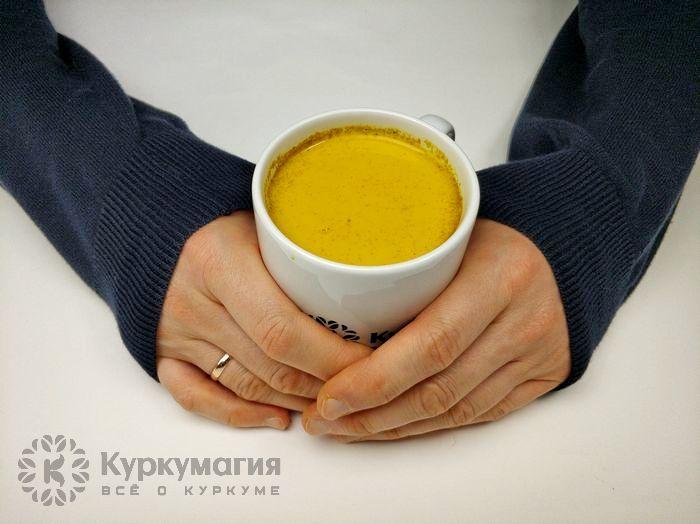 чашка с золотым молоком в руках