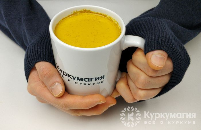 чашка с куркумой в руках